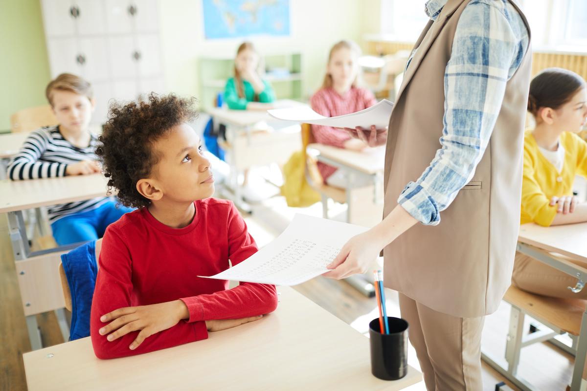 teacher praising elementary student
